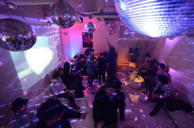 深夜のクラブで、DJ(左奥)が選曲する音楽を楽しむ人たち=2012年、東京都港区、関口聡撮影