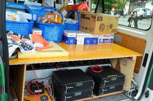 選挙カーの後部座席。栄養ドリンク、タオル、手袋が山積み=10日、岩手県内