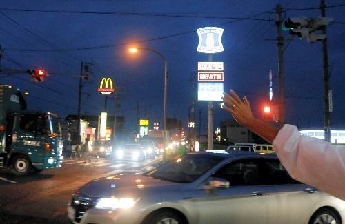秋の日はつるべ落とし。午後6時、暗くなった国道沿いで、候補者はドライバーに手を振り続けた=17日、静岡県焼津市