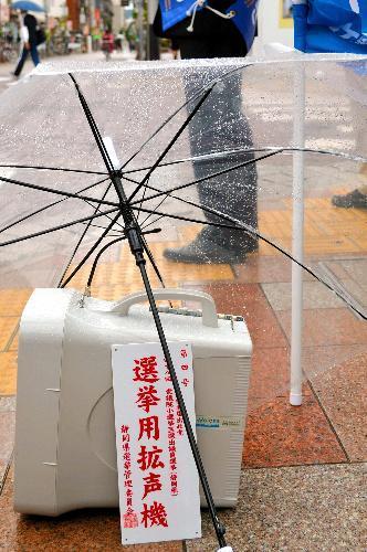 選挙戦は途中から雨続きの日々に。大切な拡声機がぬれないよう、街頭演説中は傘が立てかけられた=14日、静岡市