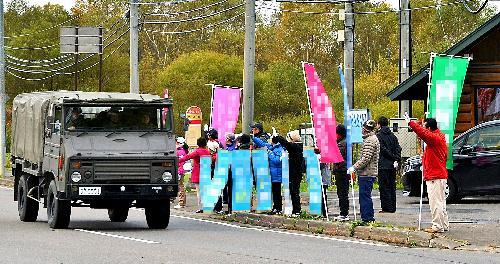 自衛隊の駐屯地近くで隊員らに手を振る候補者と支援者=13日、北海道千歳市
