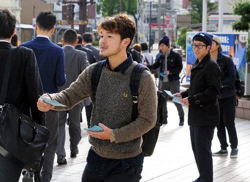 自作した投票ガイドを配る学生たち=18日、和歌山県南海和歌山市駅前