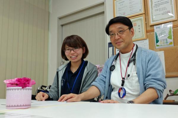 スタッフと並んで笑顔を見せる院長の小澤竹俊さん