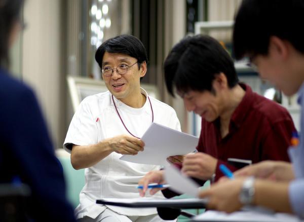 地域緩和ケア研究会で参加者と話し合う小澤竹俊さん=2015年、川村直子撮影