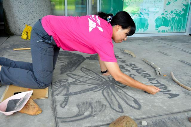 火山灰で絵を描く植村さん。火山灰を手に握って指をゆるませて灰を出しながら描く=鹿児島市、島崎周撮影