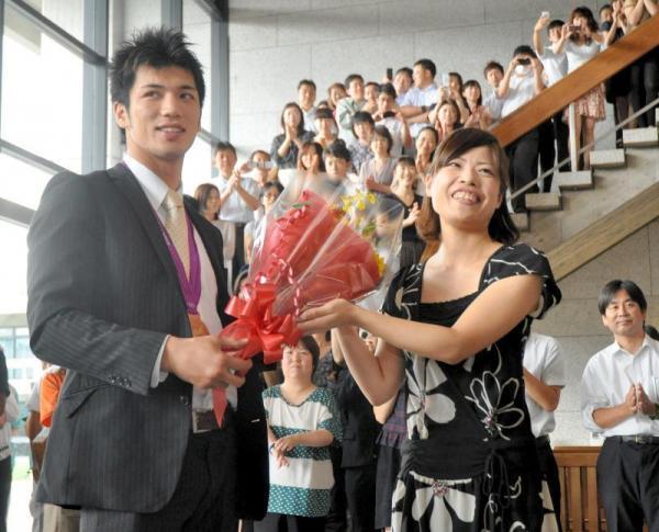 ロンドン五輪の金メダルを首にかけ、奈良県の職員らに花束と拍手で迎えられる村田諒太選手=奈良県庁