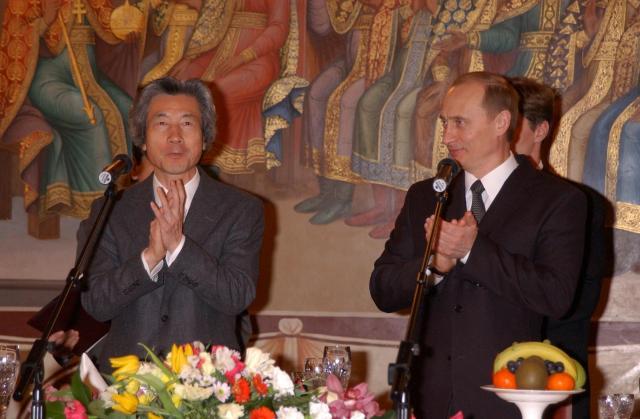 ロシア側主催の晩餐会で、プーチン大統領とテーブルで拍手する小泉純一郎首相=2003年1月10日