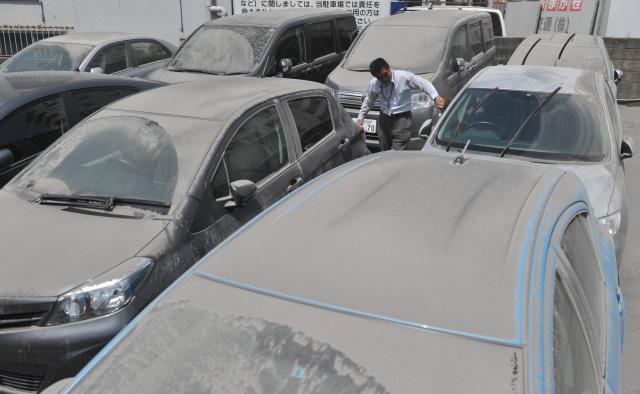 レンタカー店の車は火山灰に覆われ、従業員が清掃に追われていた=2013年、鹿児島市、池田良撮影