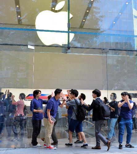 アップルの直営店に店員とハイタッチしながら入る客ら=9月22日午前8時2分、東京・表参道