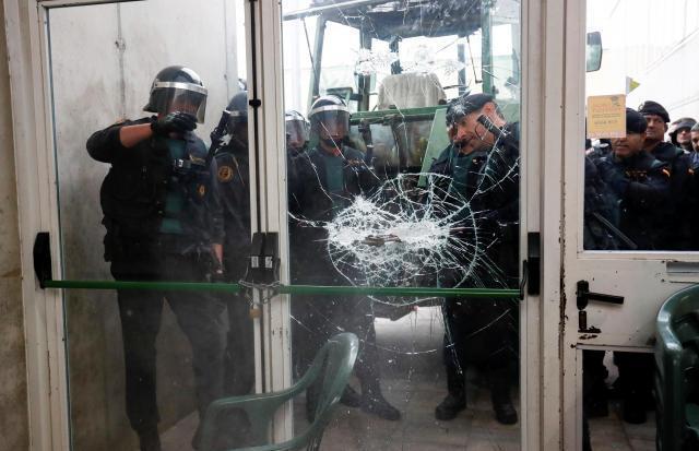 独立を問う住民投票の投票箱を撤去するために中へ入ろうと、ドアを破壊する中央政府の警官隊=2017年10月1日