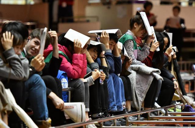 外国人客に対応するため、総務省消防庁が初めて実施した「ユニバーサルデザイン」の避難訓練。多言語によるアナウンスに従って頭部を保護する外国人観光客役の留学生たち=10月25日、東京都墨田区の両国国技館
