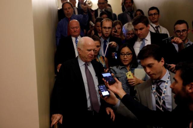 「オバマケア一部廃止」法案に反対票を投じ、記者団に囲まれるアメリカ共和党のマケイン上院議員=2017年7月28日