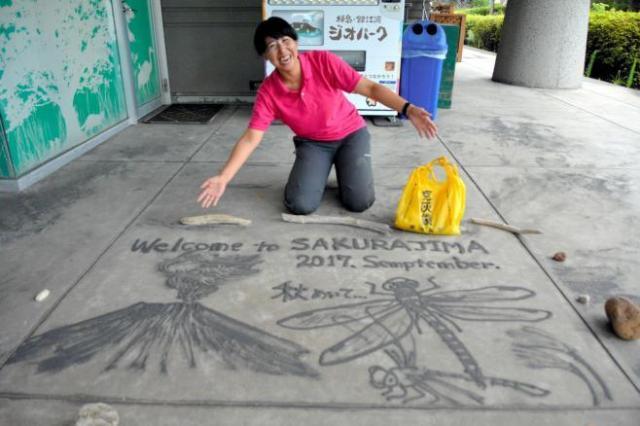 植村さんが火山灰で描いた絵。秋を意識してとんぼと桜島を描いた=鹿児島市