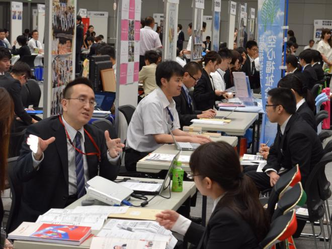 合同就職面接会で企業の「面接官」と話す=大阪市北区
