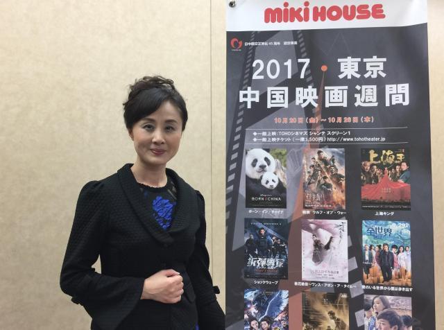 耿忠(コウチュウ)さんと東京・中国映画週間のポスター=有楽町、2017年10月26日