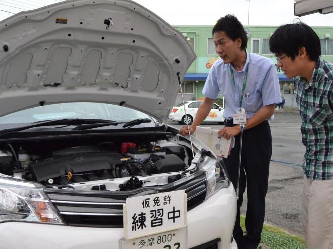 対話を重視しているという自動車教習所の「教官」(左)=東京都小金井市