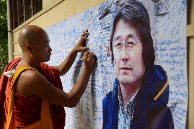 ヤンゴンで開かれた民主化運動から10年の記念セレモニー会場で、長井健司さんの写真が入った布に、「あなたのことは忘れない」などとメッセージを書き込む人たち=9月25日、染田屋竜太撮影