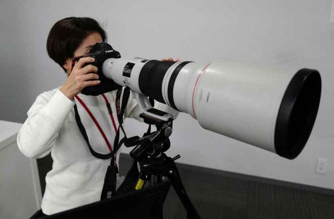 センターのカメラマン席では、600ミリの望遠レンズでこんな感じで構えます。実際にはテレコンバーターと呼ばれる、焦点距離を拡大する機器をカメラとレンズの間に装着し、約840ミリ相当の画角で撮影します=矢木隆晴撮影