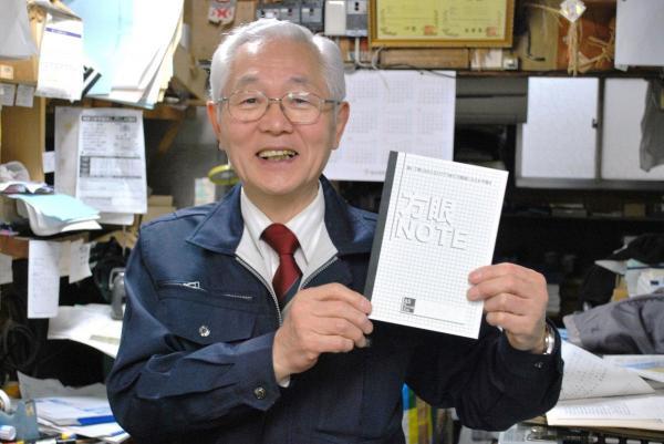 きれいに方眼ノートを手にする中村印刷所の社長・中村輝雄さん水平に開く「方眼ノート」
