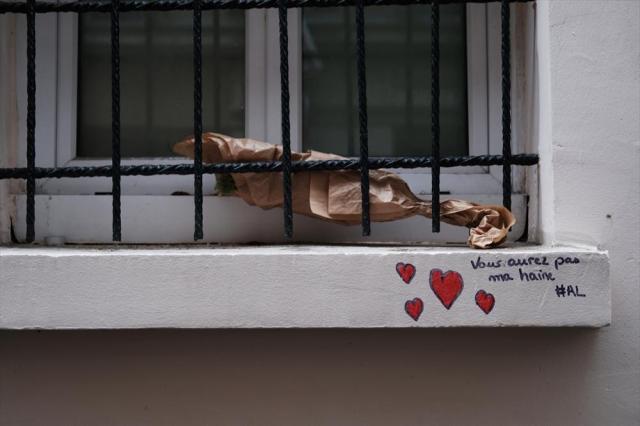 コンサートホール「ルバタクラン」の窓にはメッセージが書かれ、花が置かれていた=10月24日、フランス・パリ、竹花徹朗撮影