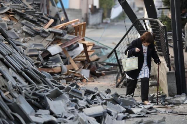 熊本県益城町で、住宅が倒壊した道路を歩いて自宅に戻る女性