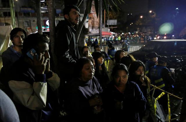 夜になっても、地震で倒壊した建物を見つめる人たち