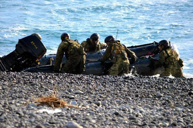 陸上自衛隊の水陸両用部隊が上陸。ボート(約150キロ)が流されないよう、銃などの装備を積んだ状態で5人ですぐ岸へ抱え上げる=11月12日、静岡県沼津市の米軍沼津海浜訓練場