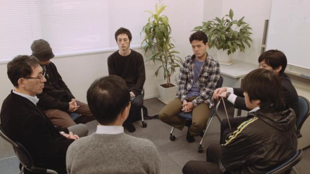 ギャンブル依存症たちの自助グループに参加する主人公(中央奥)