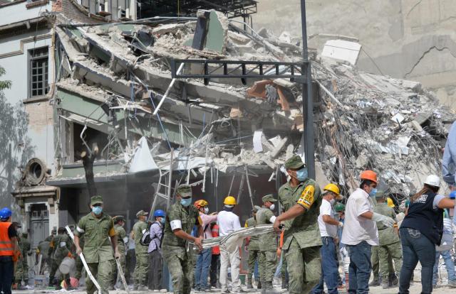 メキシコ市で、救出作業が行われているビルの倒壊現場でがれきを撤去する兵士ら