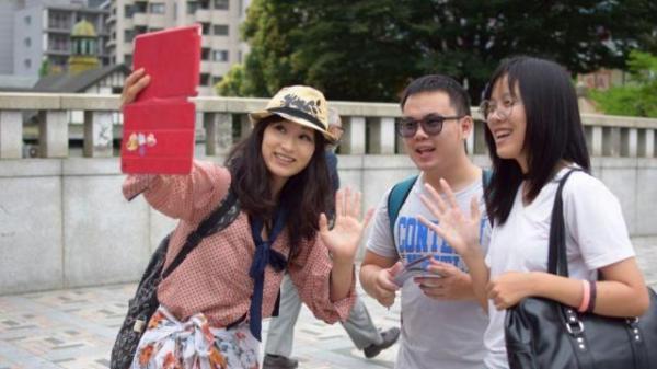 外国人と一緒に「自撮り」をする、くるみんアロマさん。ユーチューブに動画をアップすることが心の支えになった