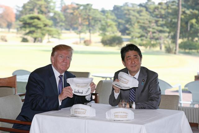 ゴルフ場での昼食前に、サインした帽子を見せる安倍首相とトランプ氏=2017年11月5日、埼玉県川越市の霞ケ関カンツリー倶楽部、代表撮影