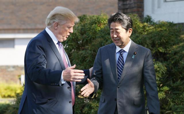 ゴルフ場で握手する安倍首相とトランプ氏=2017年11月5日、代表撮影