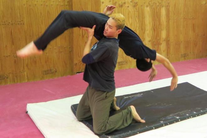 インストラクターの補助で、バク転を練習する参加者