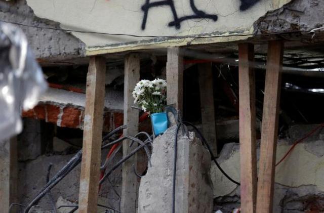 地震で崩壊した学校に手向けられた花束=2017年9月21日、ロイター