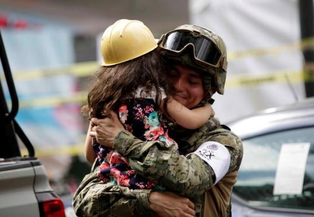子どもを抱きかかえるメキシコ海兵隊の隊員=2017年9月24日、ロイター