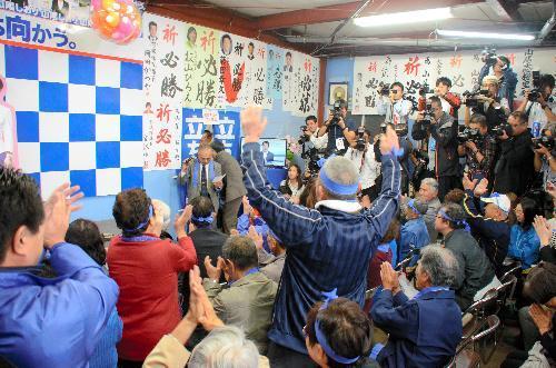 山尾氏のリードが伝えられ、思わず万歳する支援者=愛知県長久手市