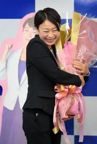 当選を決め、花束を抱いて喜ぶ山尾志桜里氏=愛知県長久手市、川津陽一撮影