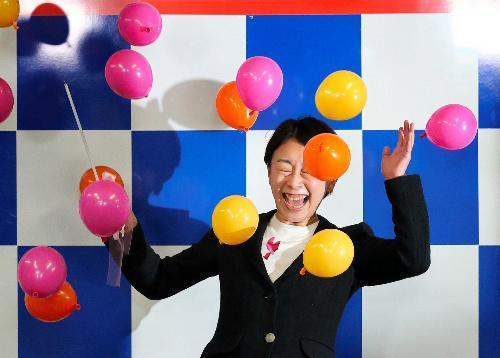当選を決め、くす玉を割って喜ぶ山尾志桜里氏=愛知県長久手市、川津陽一撮影