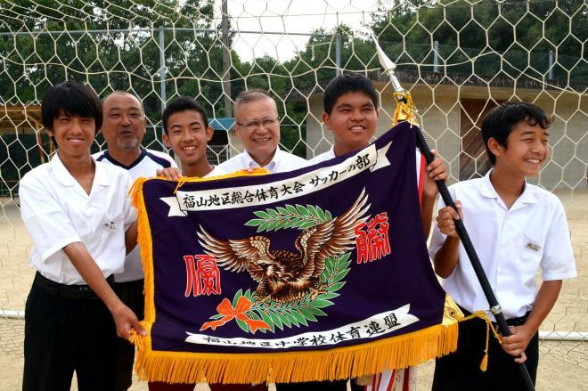 友道健氏さん(右から3人目)は闘病中に一時退院して中学校を訪れ、サッカー部を激励した=7月28日、広島県福山市の大成館中学校