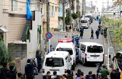 遺体が見つかったアパート(左)付近に集まる警察車両と捜査員=2017年10月31日、神奈川県座間市、長島一浩撮影