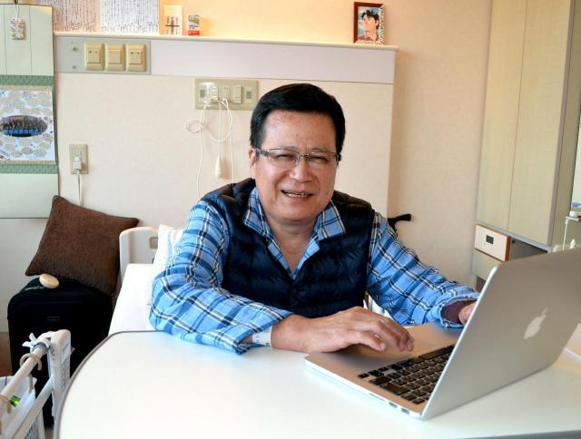 入院中の友道健氏さん。パソコンを使って、病室からメールやフェイスブックで闘病の様子を知人らに伝えていた=6月3日、岡山県倉敷市