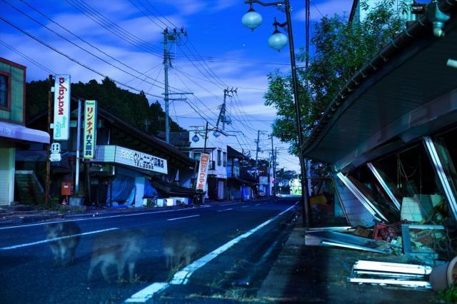 月明かりに照らされた双葉町の商店街。一部の建物は崩れたまま。イノシシの姿も写っていた=10月4日、福島県双葉町(30秒間露光)