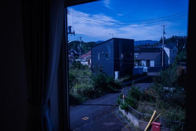2階の窓から見える、夜の新興住宅地。人の手が入らない庭は雑草に覆われている=福島県双葉町