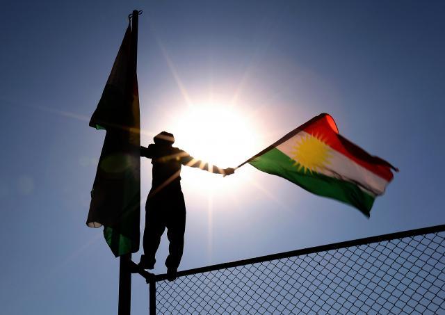 イラク北部アルビルで開かれた独立賛成派の集会でフェンスに登り、KRGの旗を振る参加者=2016年9月22日