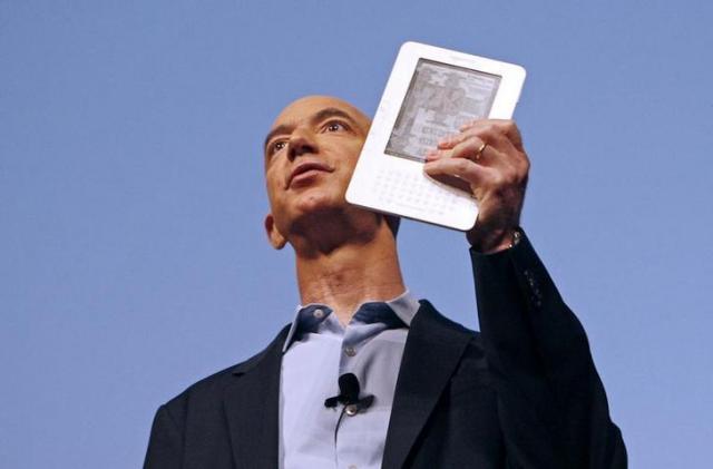 電子書籍「Kindle」を手にするアマゾンのジェフ・ベゾス氏=ロイター