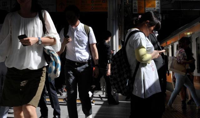 駅のホームでスマホを手に歩いたり電車を待ったりする人たち