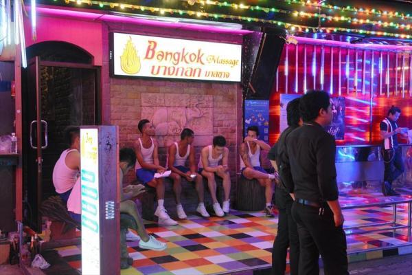 「ソイトゥワイライト」と呼ばれるバンコクの歓楽街に軒を連ねるゴーゴーボーイ(男娼の連れだしバー)。店の外で客待ちをしているのか、タトゥーを入れた男たちが携帯電話を操作していた=撮影、水谷