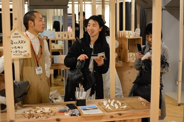 SNSで出店を知り訪れた客と交流する出店者(左)