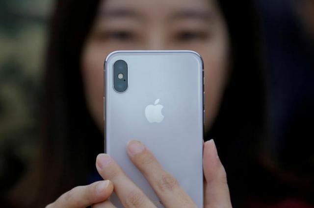 新型の「iPhone X」を使う女性=北京、ロイター