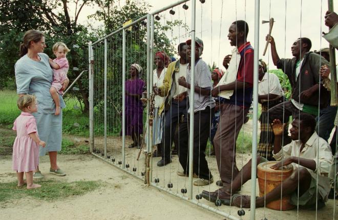 ジンバブエ北部の農場で、侵入してきた黒人たちをフェンス越しに眺める白人農場主の家族=2000年3月29日